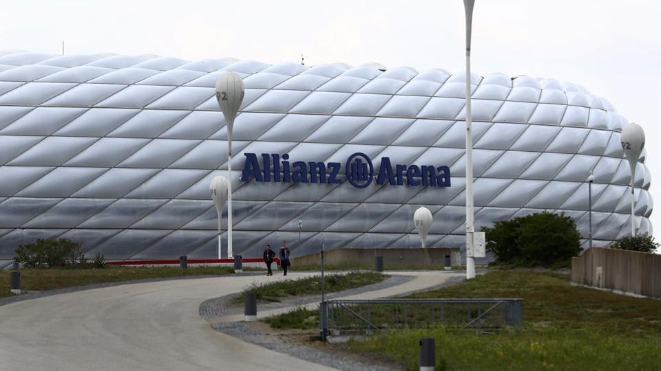 People pass the German Bundesliga soccer club stadium 'Allianz Arena' in Munich, Germany, Tuesday, April 28, 2020.