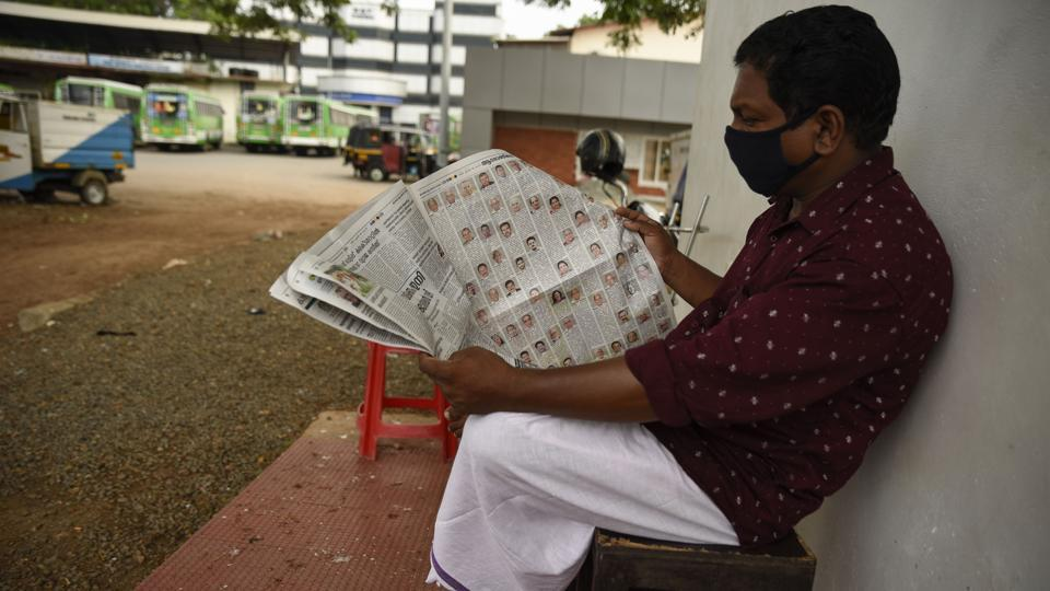 A man wearing a mask reads a newspaper at a bus terminus which has been shut down for more than a month as part of measures to curb the spread of the COVID-19 pandemic in Kochi, Kerala.