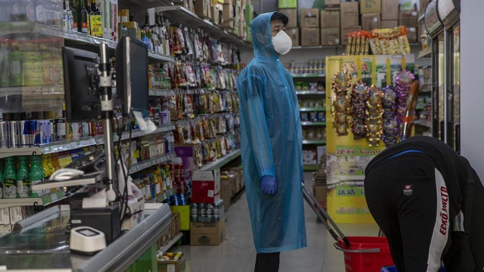 A man wearing a face mask buys items in a supermarket in Madrid, Spain.