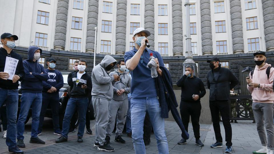 Wearing surgical masks, demonstrators briefly blocked traffic outside a government building in the city centre in defiance of rules against public gatherings.