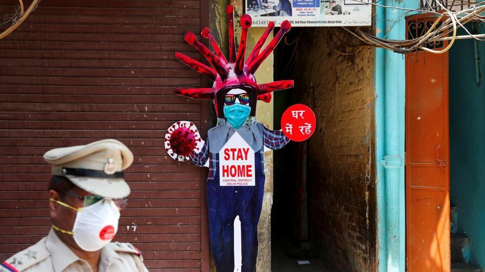 A police officer wearing a protective face mask walks past a novel coronavirus-themed scarecrow cutout put up in a residential area during an extended lockdown to slow the spreading ofthe coronavirus disease (COVID-19) in the old quarters of Delhi.
