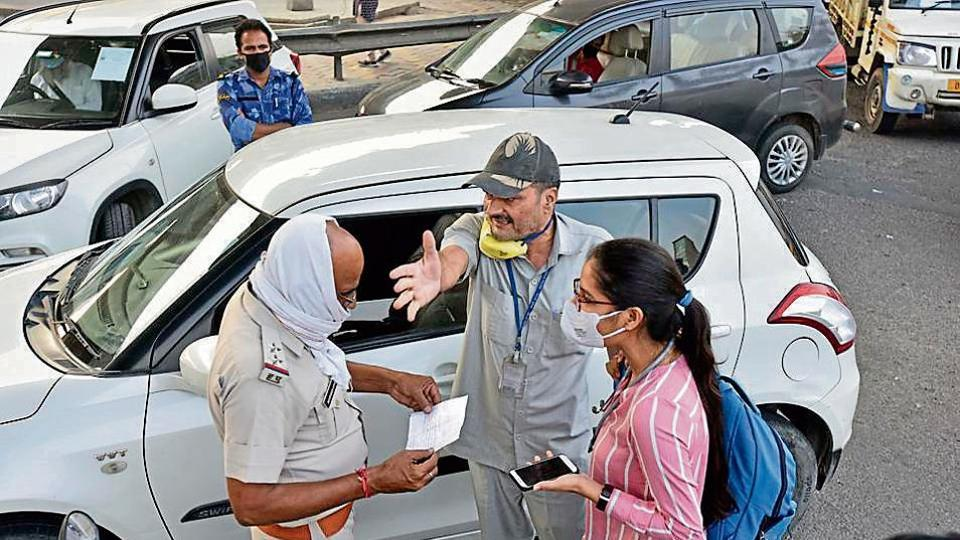 A policeman checks the curfew pass of a commuter at the Delhi-Faridabad border. Faridabad on Wednesday shut its border withDelhi to insulate itself from Covid-19 cases.