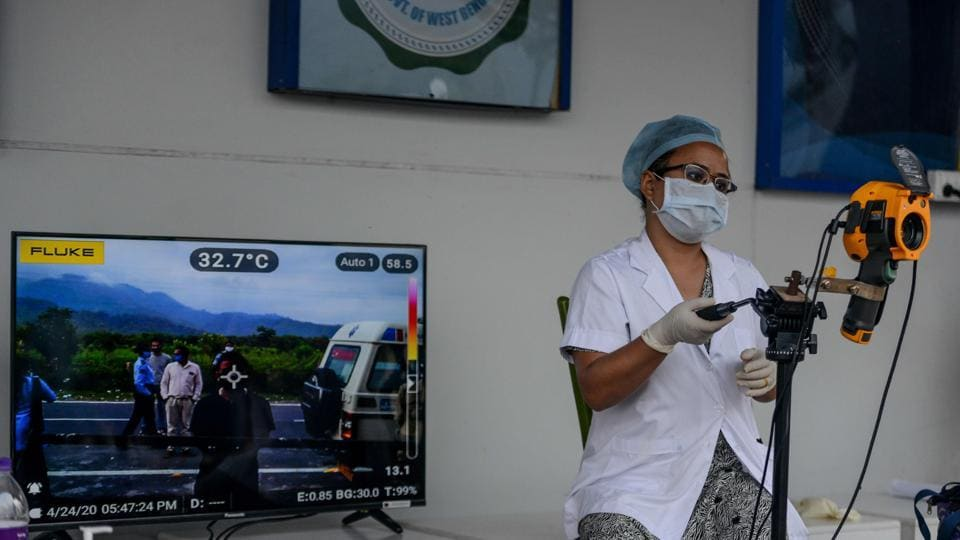 A medical staff uses a thermal scanner at an information collection and awareness desk set up by the West Bengal Health Department of Darjeeling district during a government-imposed nationwide lockdown as a preventive measure against the COVID-19 coronavirus, in Simulbari village on the outskirts of Siliguri.