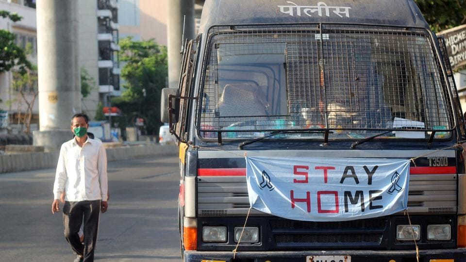 A man walks past a police van with Stay Home message, during the Covid-19 lockdown in Mumbai on Wednesday.