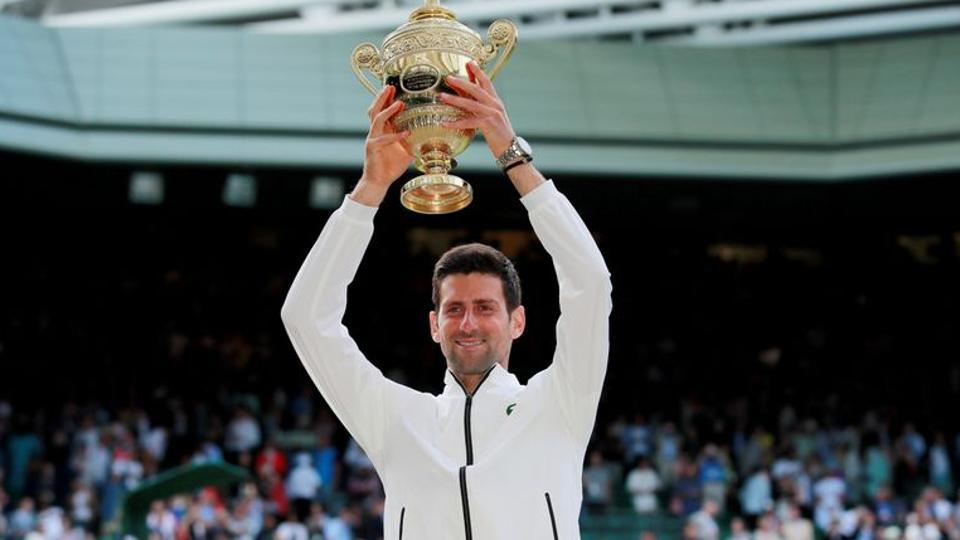 FILE PHOTO: Tennis - Wimbledon - All England Lawn Tennis and Croquet Club, London, Britain - July 14, 2019 Serbia's Novak Djokovic with the trophy as he celebrates winning the final against Switzerland's Roger Federer REUTERS/Andrew Couldridge/File Photo