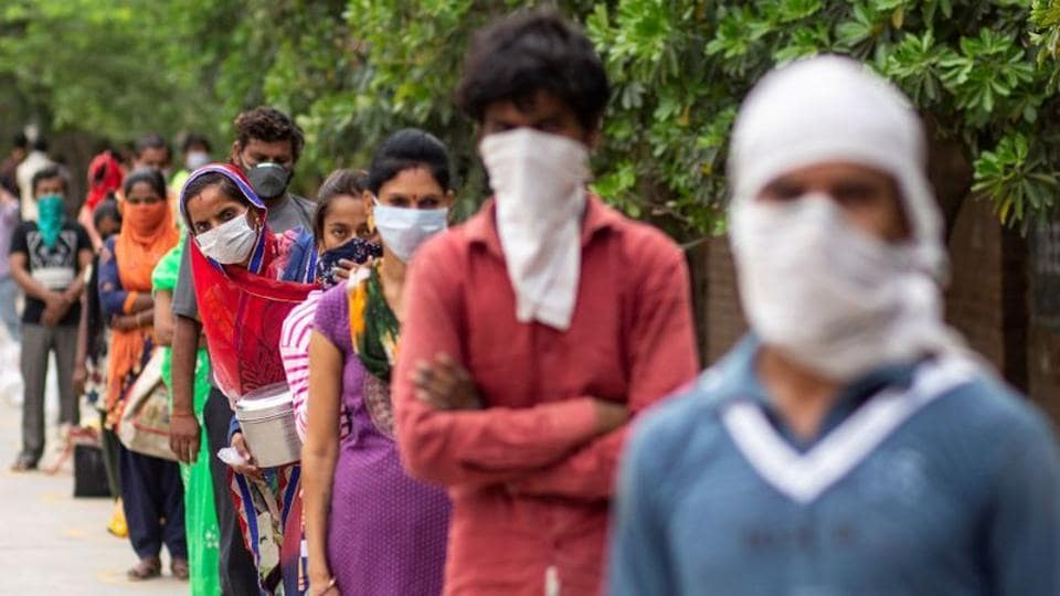 Covid-19 lockdown updates: People wait to receive free food at an industrial area, during an extended nationwide lockdown to slow the spreading of the coronavirus disease (COVID-19) in New Delhi, India, April 23, 2020.