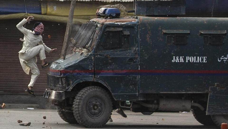 A masked Kashmiri protester jumps on the bonnet of a vehicle belonging to the security forces as he throws stones at it during a protest in Srinagar on  May 31, 2019. The image was part of a series of photographs by Associated Press photographers which won the 2020 Pulitzer Prize for Feature Photography. (Dar Yasin / AP)