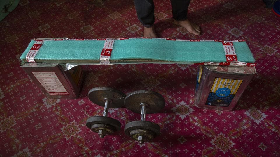 Weightlifter Bashir Ahmed has fashioned a makeshift bench of tin boxes and a wooden plank covered with thermocol inside his room in Srinagar. (Dar Yasin / AP)