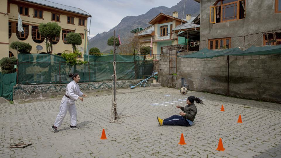 Football coach Qudsiya Altaf (R), and her sister Kabra Altaf, a judo champion, practice inside a school compound that belongs to their father, near their home in Srinagar. The sisters are restricted to their neighbourhood but the lockdown is nothing new. (Dar Yasin / AP)