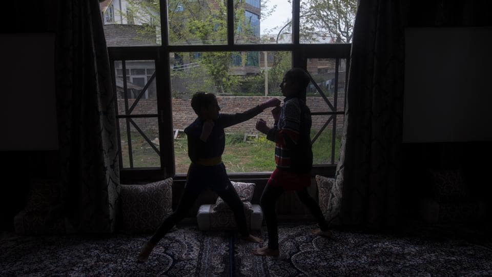 Wushu artist Aliza Shah (L), spars with her sister Kaifa Shah inside their home in Srinagar. Going out for practice is too high a risk but the athletes' priority remains to keep fit. (Dar Yasin / AP)