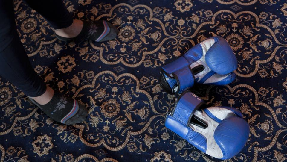 Eyed Akeel Khan's boxing gloves lie on the floor of the room where he practices at home in Srinaga. The carpet in his room has replaced the boxing ring. (Dar Yasin / AP)