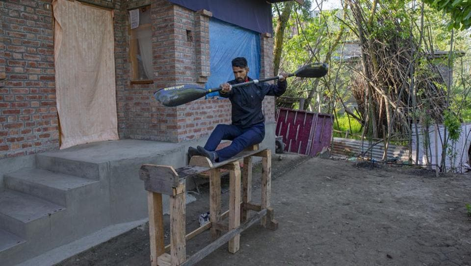 "Kashmiri kayaker Vilayat Hussain practices on a rugged under-construction wooden ergometer at his home on the outskirts of Srinagar. Like many other athletes, the coronavirus pandemic has restricted Hussain to his home. ""It (the wooden ergometer) helps me to maintain my workouts even though it is far from what it should look like,"" Hussain told AP. (Dar Yasin / AP)"