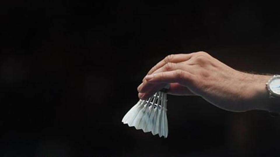 A match official places a new shuttlecock on a racket