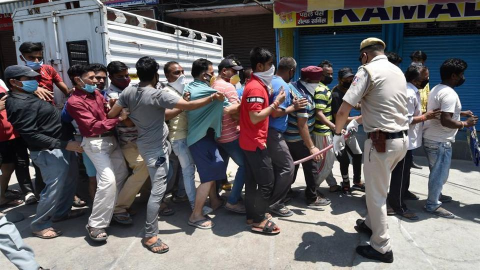 Police try to control the crowd as people stand in a queue, flouting social distancing measures, to buy alcohol in Delhi on Tuesday.