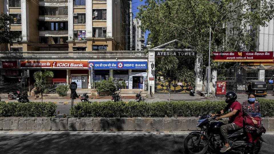 A motorcyclist and passenger travel past branches of ICICI Bank Ltd., HDFC Bank Ltd. and Punjab National Bank (PNB) on a near-empty street in Mumbai.