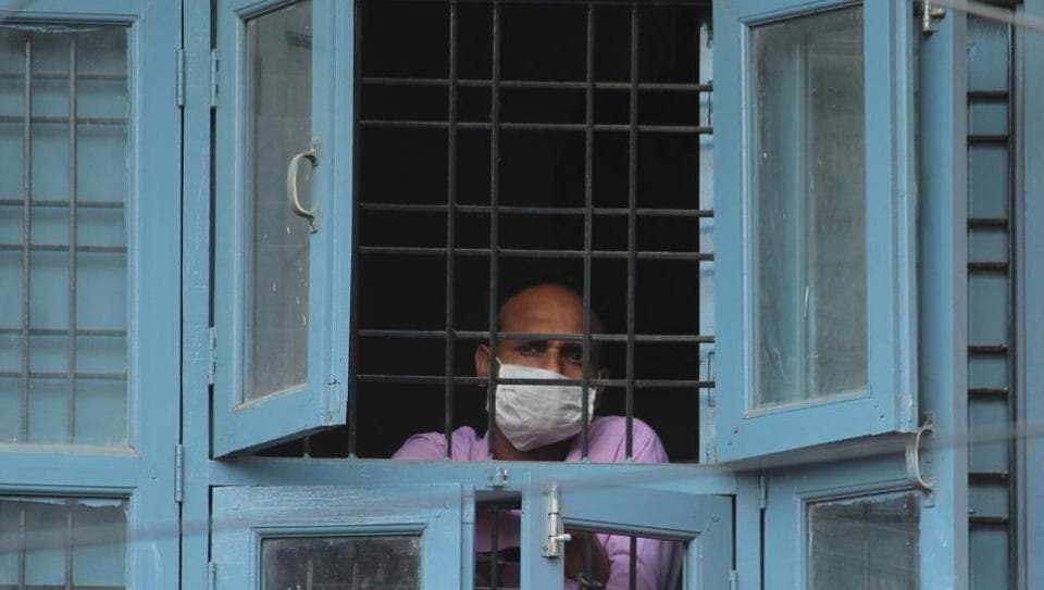 A resident looks out from a window, during nationwide lockdown to check the spread of coronavirus, at Sirhaul village, in Gurugram, India, on Tuesday, 05 May 2020.