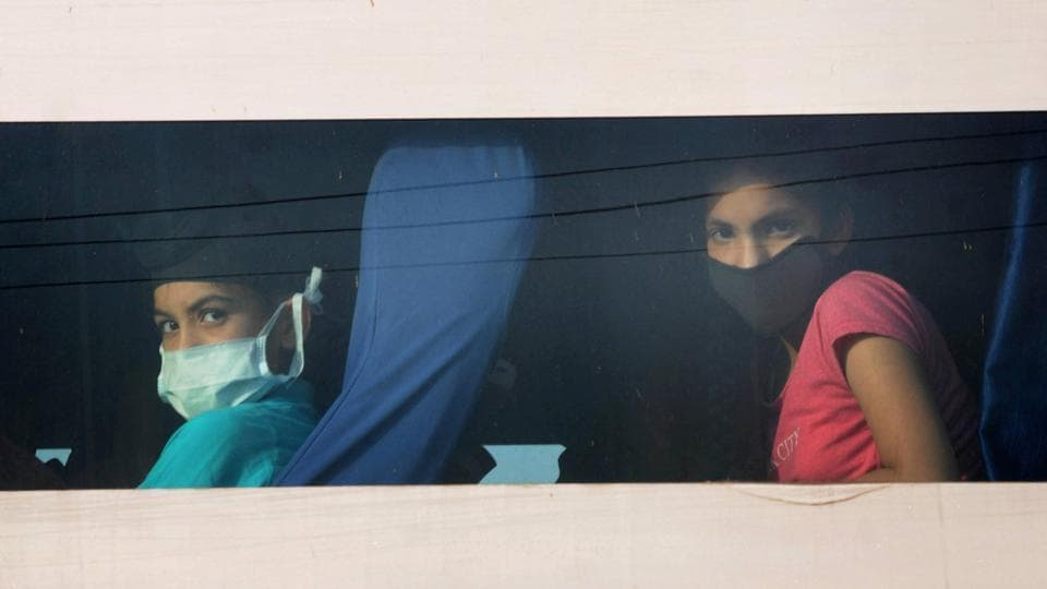 Passengers look out from the window of a bus, after Punjab government subjected them to a mandatory 21-day quarantine in the wake of coronavirus pandemic in Amritsar on April 29, 2020. The passengers were travelling from Nanded in Maharashtra.