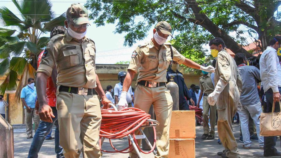 Police carry equipments after a styrene vapour leak from a polymer plant in Visakhapatnam.