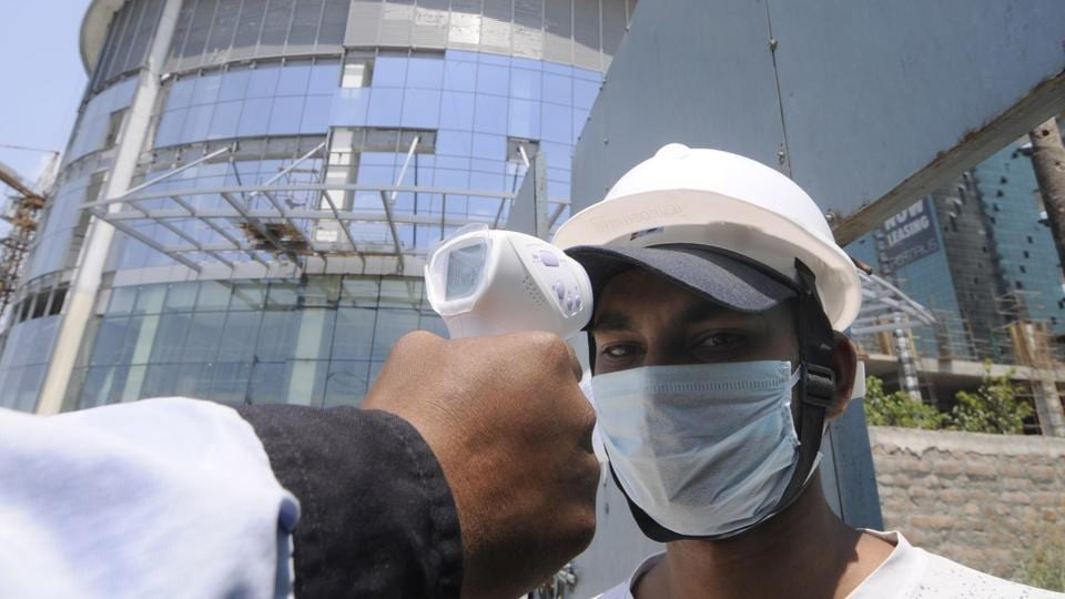A worker undergoes thermal screening at an under construction site during lockdown, at at Supertech Supernova, Sector 94.