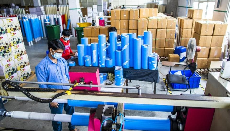 A worker wearing a protective mask operates a tape cutting machine while producing adhesive sealing tapes at a factory in Sonipat district, Haryana