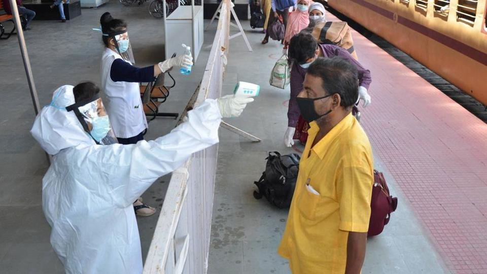 Medics screen migrant people on their arrival at Hatia Railway Station by a special train from Tamil Nadu, amid ongoing COVID-19 lockdown in Ranchi, Friday, May 8, 2020.