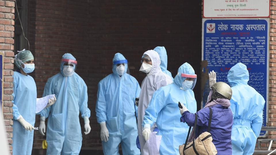 Medical professionals interact with visitors outside the Covid-19 ward during lockdown at LNJP hospital, New Delhi.