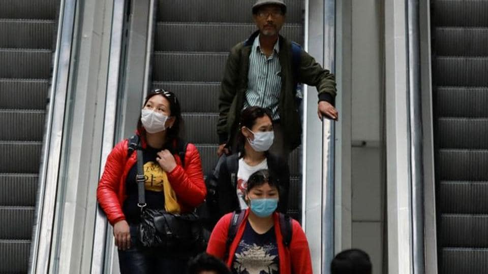 Passengers wearing protective masks travel on an escalator at an airport terminal following an outbreak of the coronavirus disease (COVID-19), in New Delhi, India, March 14, 2020. REUTERS/Anushree Fadnavis