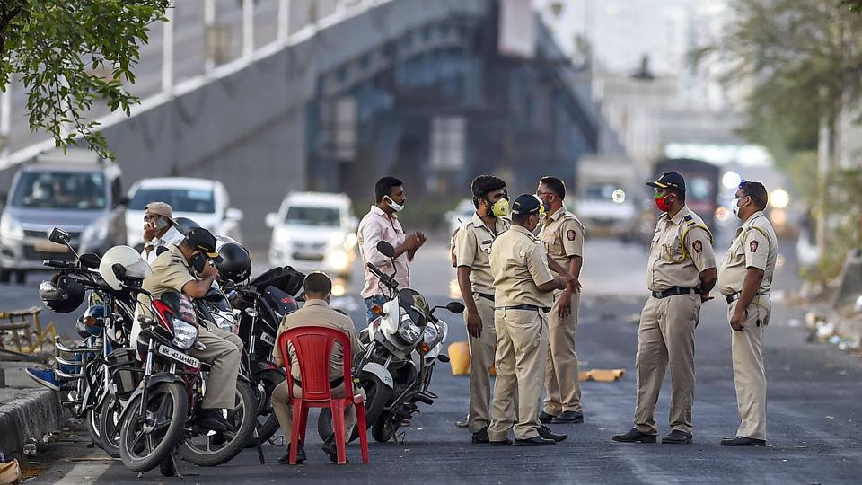Police personnel stop migrants on their way back to reach native places on Eastern Express Highway, in Mumbai on Sunday.