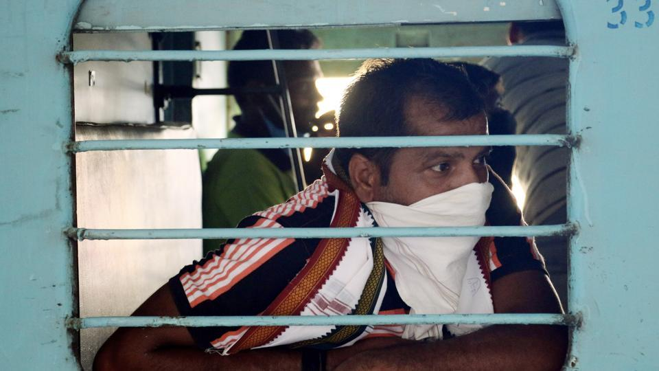 A migrant worker peeps out of the window as he boards a special train to go to native place in Bihar from Ajmer on Sunday.