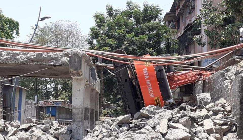 The excavator lost control and fell on the road below the under-construction Dombivli rail  overbridge.