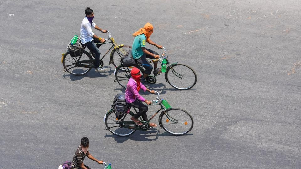 Migrants riding bicycles from Chennai on their way to their native places in Odisha pass through Vijayawada,.