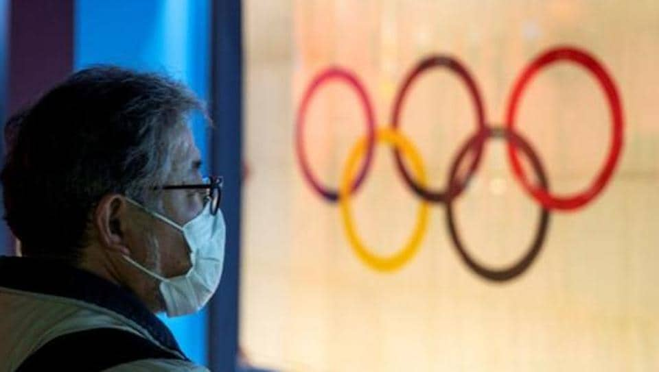 A man wearing a protective face mask, following an outbreak of the coronavirus, stands in front of The Tokyo Olympic flag 1964 at The Japan Olympics museum in Tokyo.
