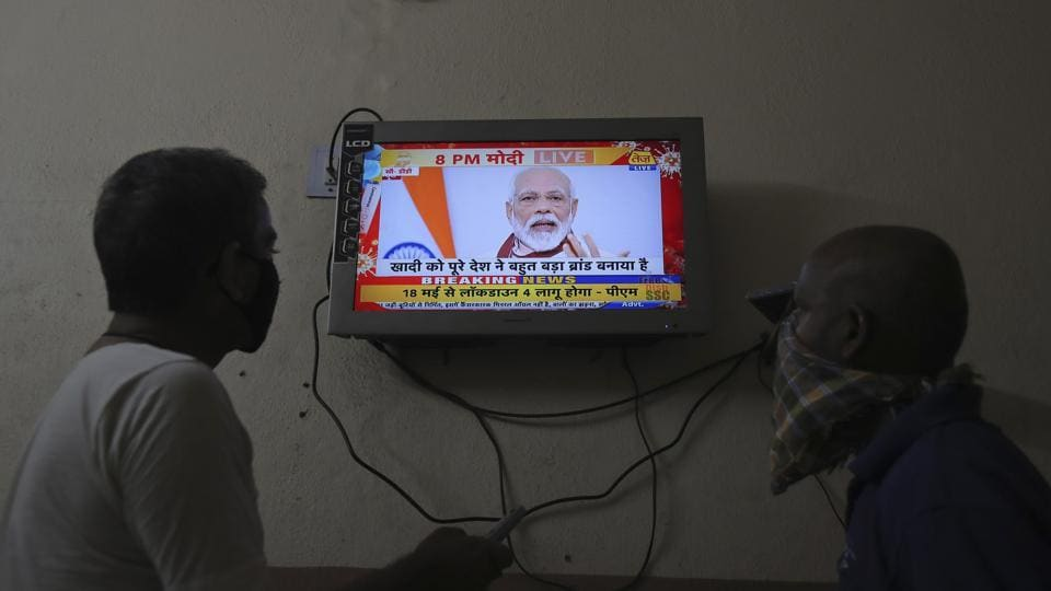 Indians watch a televised address to the nation by Prime Minister Narendra Modi in Hyderabad, India.