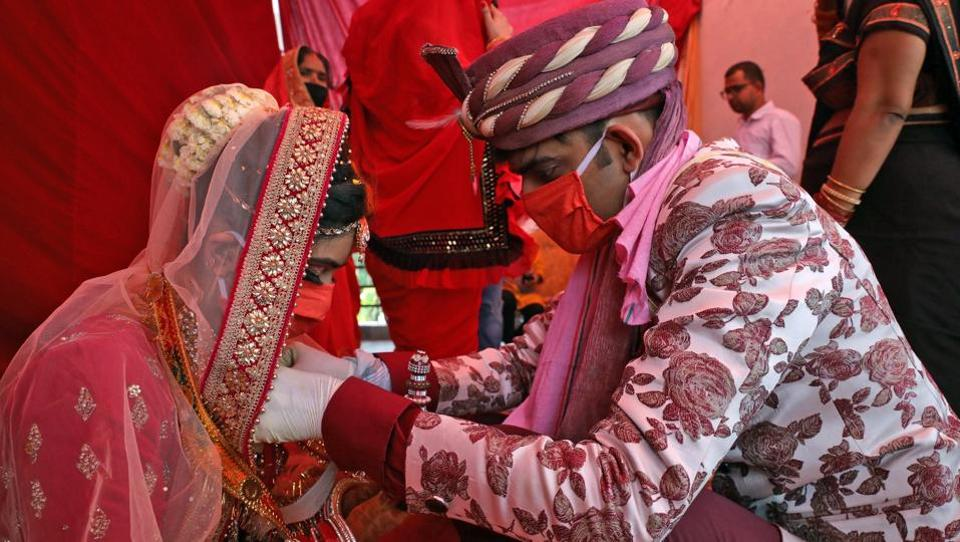 An Indian couple performs marriage rituals wearing protective masks in New Delhi. As the lockdown prevails, couples do not have much choice except postponing their wedding or opting for a simple one.  (ANI)