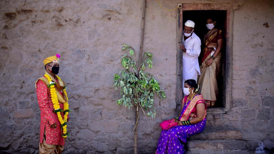 Groom Vitthal Koditkar (L) of Hirpodi village speaks with his bride Vrushali Renuse (R) of Pabe village and family members after their wedding in the middle of a nationwide lockdown, in Pune.  (Sanket Wankhade / AFP)