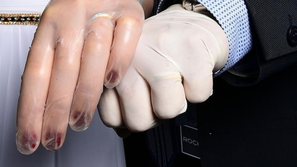 Newly-wed Italians Ester Concilio (L) and Rafaele Carbonelli show wedding rings under the protective gloves following the ceremony at the Briosco's town hall, on May 11. In light of the Mayor's restricting any ceremonies during the lockdown, the couple decided to get married without a banquet or any guests.  (Miguel Medina / AFP)
