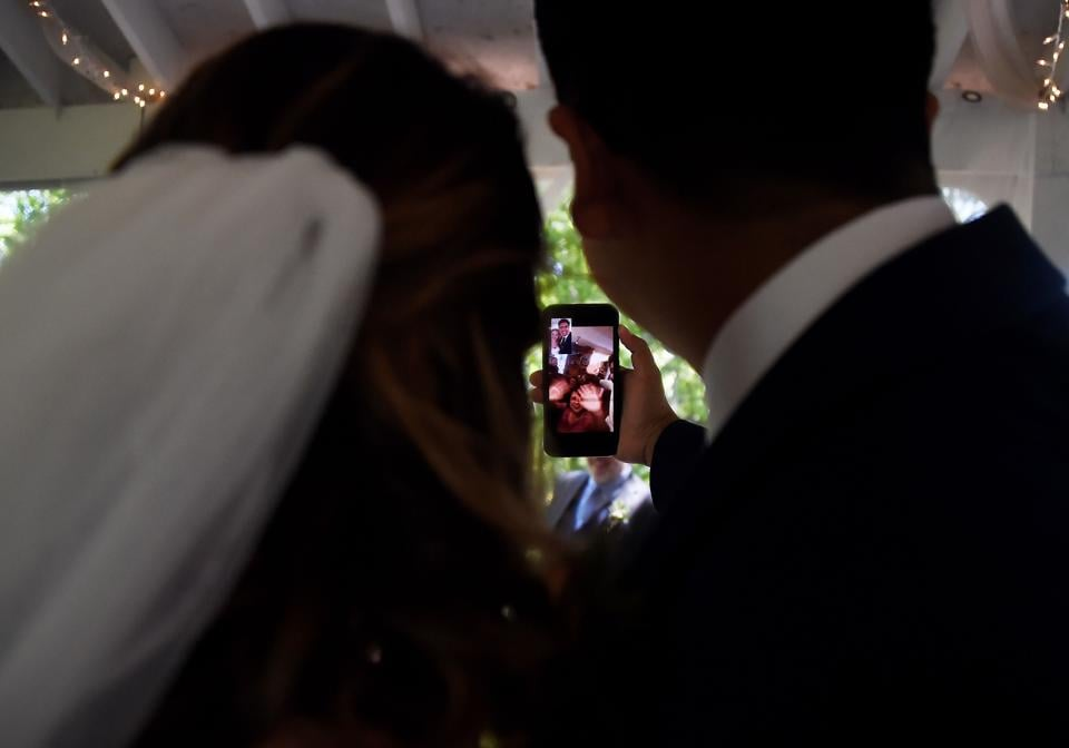 Newly married couple Rachel and Sebastian Vasquez talk (via Facetime) to relatives who could not attend their wedding ceremony on May 9 at the Glencliff Manor in Rustburg, Virginia. The Glencliff Manor officiates free, socially distanced ceremonies for couples left with no wedding plans during the coronavirus pandemic. Only ten people are allowed at each hour-long ceremony.  (Olivier Douliery / AFP)