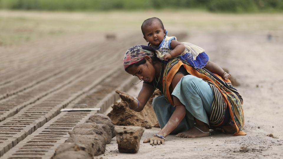An Indian woman works at a brick kiln as he child plays on her back during lockdown to curb the spread of new coronavirus on the outskirts of Jammu, India.
