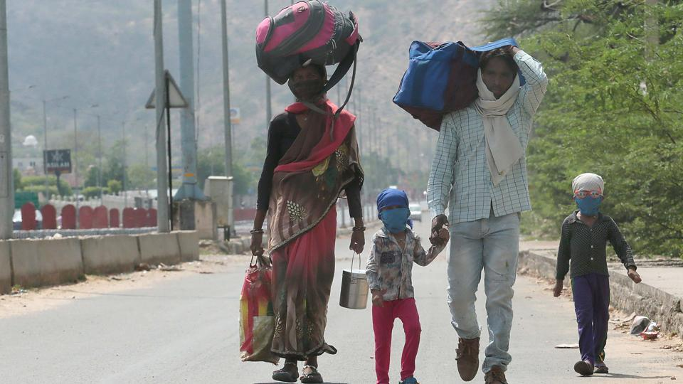 A migrant labourer, 25-year-old Naresh and his 8-month pregnant wife Malti along with son Pradeep and daughter Tanu, while walking towards their home in Chhatarpur district of Madhya Pradesh, on Agra highway during third phase of Lockdown due to corona pandemic, in Jaipur, India on Thurssday, 14 May 2020.