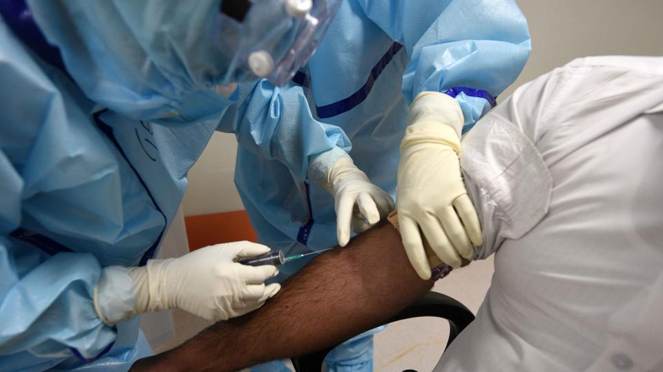 Medical professionals collect blood sample from a suspected COVID-19 patient, in Institute of Liver and Biliary Science (ILBS) hospital, New Delhi.