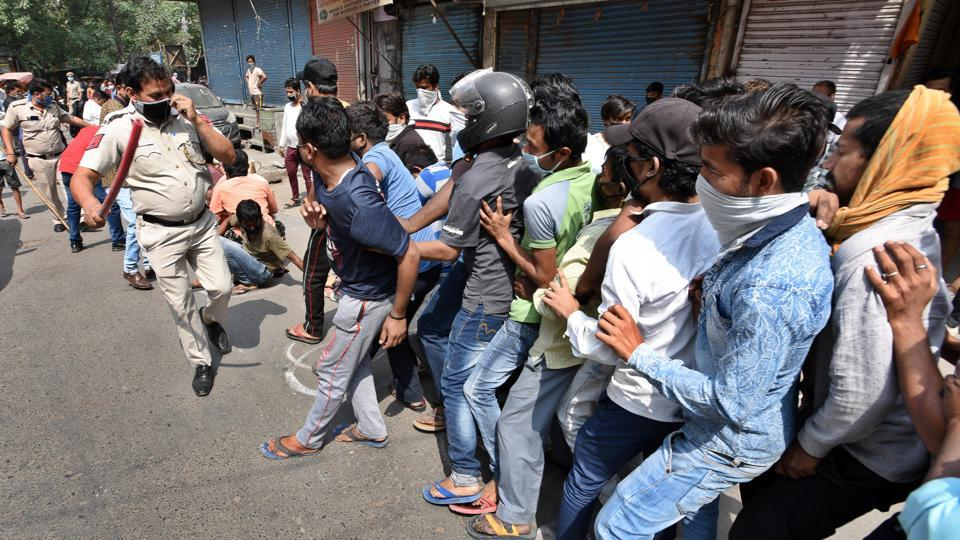 Police personnel wield lathis in an attempt to ensure social distance in a large crowd queued outside a liquor shop in Jheel Chowk after relaxations allowed their opening, in New Delhi.