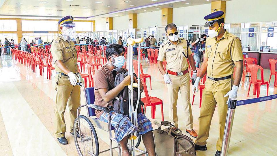Kerala police personnel led by Inspector General of Police Vijay Sakhare (second from right)  assist a differently-abled man after being disembarked by INS Jalashwa carrying repatriated Indian citizens from Maldives, at Cochin Port.