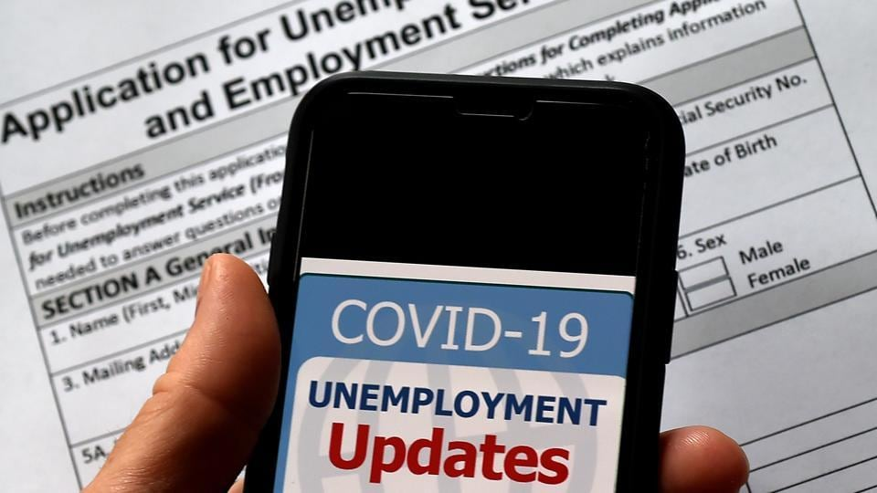 (FILES) In this illustration file photo taken on May 08, 2020, a COVID-19 Unemployment Assistance Updates logo is displayed on a smartphone on top of an application for unemployment benefits, in Arlington, Virginia.