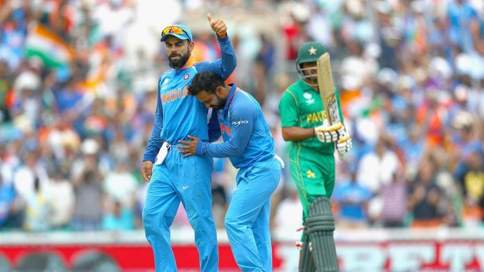 Kedar Jadhav of India celebrates the wicket of Babar Azam of Pakistan with Virat Kohli during the ICC Champions trophy cricket match between India and Pakistan at The Oval in London on June 18, 2017 (Photo by Clive Rose/Getty Images)