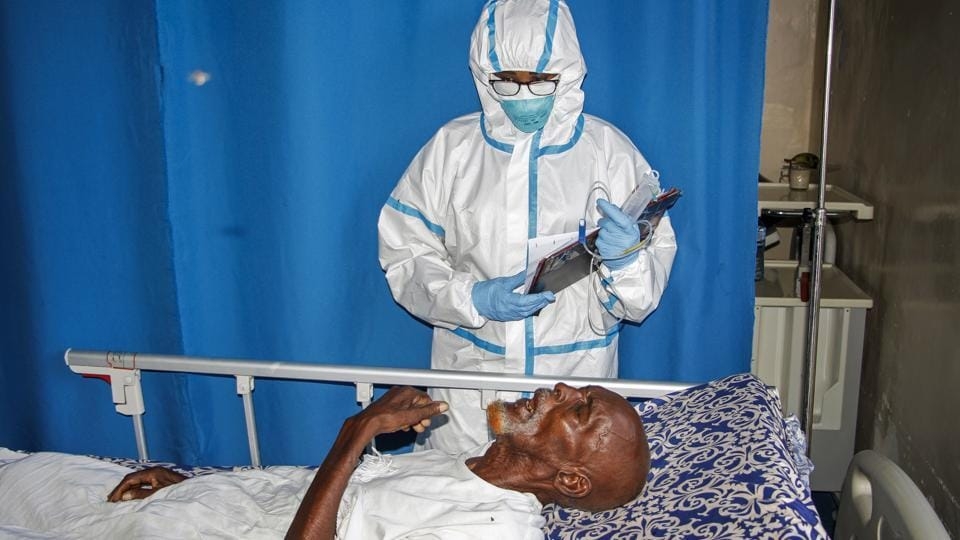 In this photo taken Wednesday, May, 13, 2020, a doctor tends to a patient in a ward for coronavirus patients at the Martini Hospital in Mogadishu, Somalia. Years of conflict, instability and poverty have left Somalia ill-equipped to handle a health crisis like the coronavirus pandemic.
