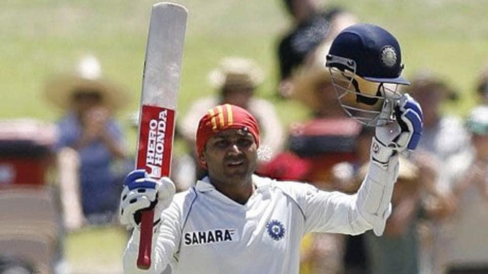 Virender Sehwag raises his bat after scoring a century