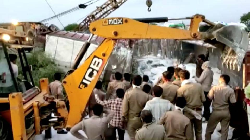 A police rescue team work to lift a truck at the site of an accident where a truck carrying migrant labourers collided with another, killing 24 and injuring several people in Auraiya, Uttar Pradesh.