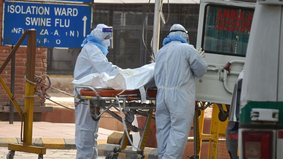 Health workers wearing protective suits shift to a van the body of a coronavirus victim, at LNJP Hospital in New Delhi.
