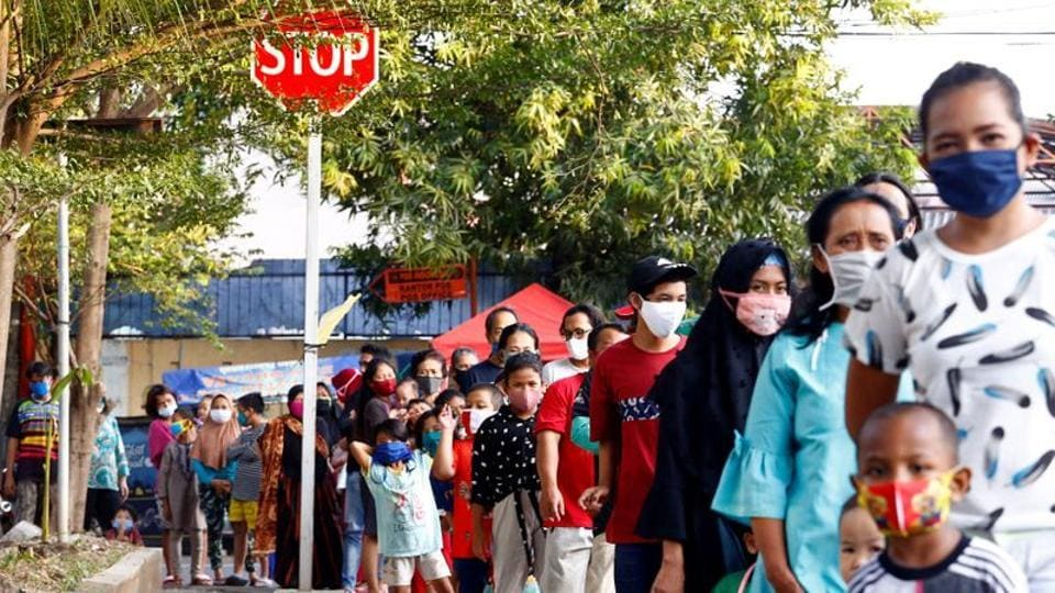 People wearing a protective face mask stand in line to get free food amid the coronavirus disease (COVID-19) outbreak in Jakarta, Indonesia, May 14, 2020.