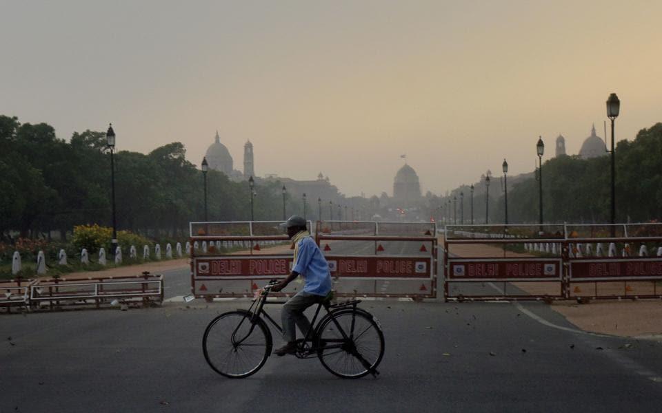 A cyclist rides amid a dust-storm on Rajpath in New Delhi.
